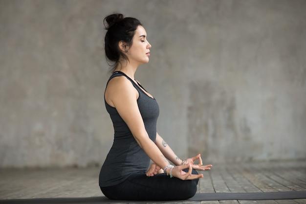 Jeune femme, faire, sukhasana, exercice, vue côté Photo gratuit