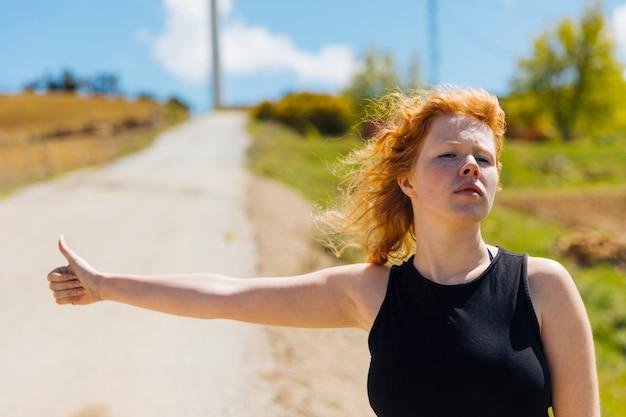 Jeune Femme Faisant De L'auto-stop Sur Le Bord De La Route Photo gratuit