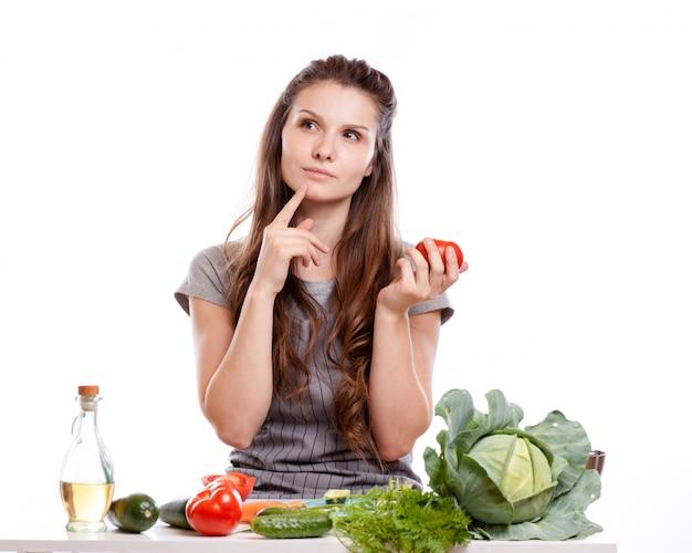 Jeune femme faisant la cuisine dans la cuisine. alimentation saine - salade de légumes. régime. concept de régime. Photo Premium