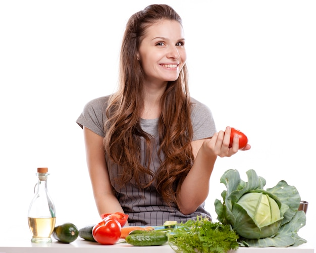 Jeune femme faisant la cuisine dans la cuisine. alimentation saine - salade de légumes. Photo Premium