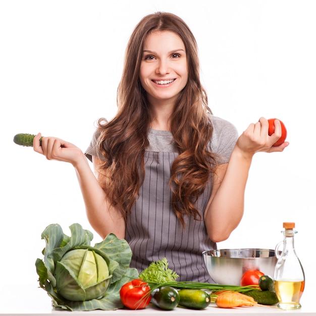 Jeune femme faisant la cuisine dans la cuisine. la nourriture saine Photo Premium