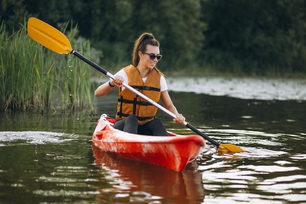 Jeune femme faisant du kayak sur le lac Photo gratuit