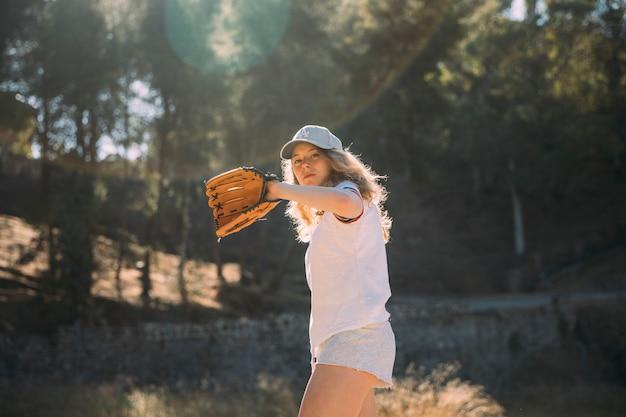 Jeune femme faisant du terrain de baseball Photo gratuit