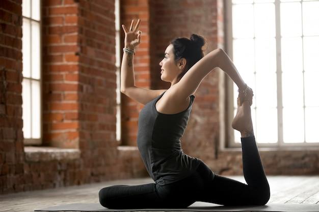 Jeune femme faisant un exercice à une jambe du roi pigeon Photo gratuit