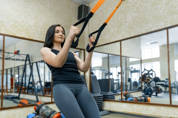 Jeune femme faisant des exercices à l'aide du système de sangles Photo Premium
