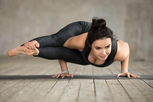Jeune femme faisant des exercices d'astavakrasana Photo gratuit