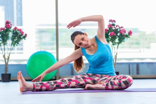 Jeune femme faisant des exercices dans le concept de santé de gym Photo Premium