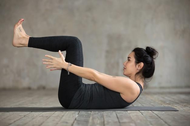 Jeune femme faisant des exercices de navasana Photo gratuit
