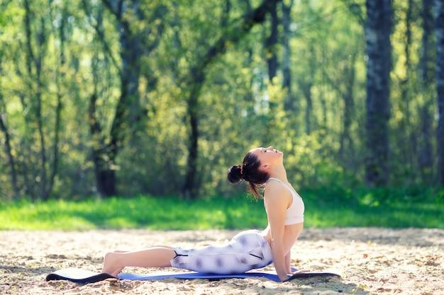 Jeune femme faisant des exercices de yoga dans le parc de la ville d'été Photo Premium