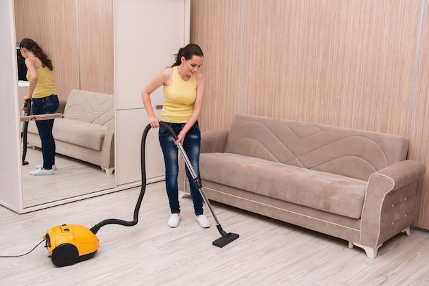 Jeune femme faisant le ménage à la maison Photo Premium