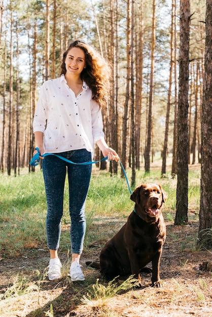 Jeune femme faisant un pique-nique avec son chien Photo gratuit