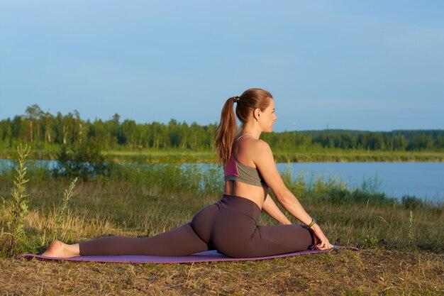 Une Jeune Femme Fait Du Yoga Dans La Nature.yoga Pose Et Pratique. Photo Premium