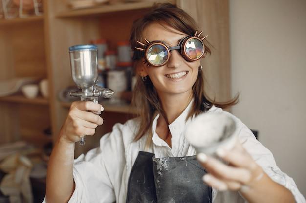 Jeune femme fait de la poterie en atelier Photo gratuit