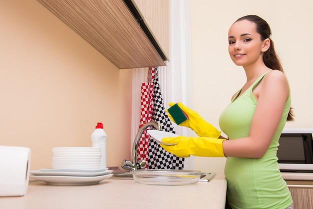 Jeune femme femme, laver la vaisselle dans la cuisine Photo Premium