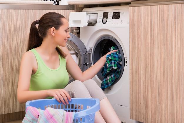 Jeune femme femme laver les vêtements près de la machine Photo Premium