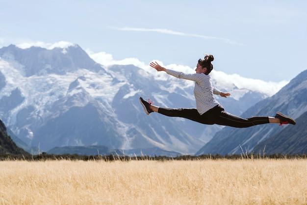 Jeune femme férue de yoga et de gymnastique faisant un saut parfait dans la nature sauvage. Photo Premium