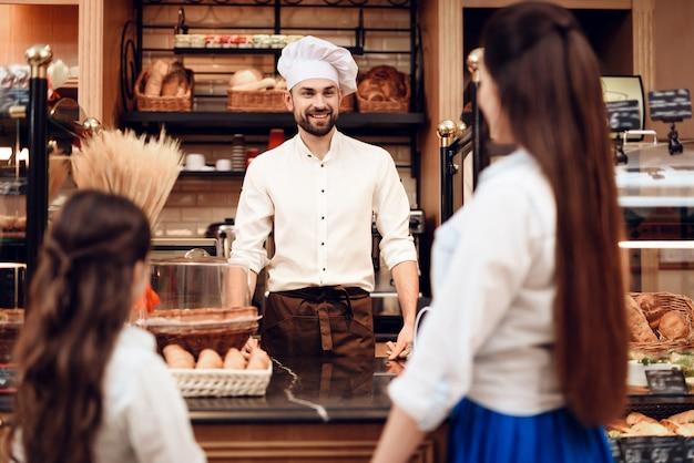 Jeune femme avec fille acheter du pain en boulangerie. Photo Premium