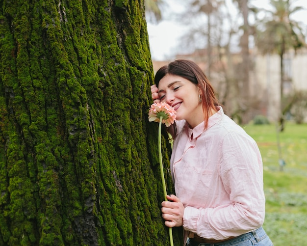 Jeune femme avec une fleur se penchant sur un arbre Photo gratuit
