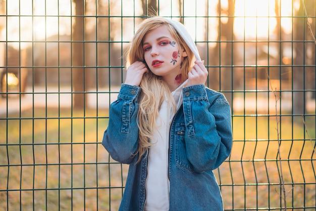 Jeune femme avec des fleurs peintes temporaires sur le visage. adolescente aux longs cheveux blonds porter une veste en jean et capuche Photo Premium