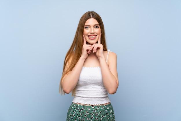 Jeune femme sur fond bleu isolé, souriant avec une expression heureuse et agréable Photo Premium