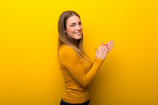 Jeune femme sur fond jaune applaudissant après présentation à une conférence Photo Premium