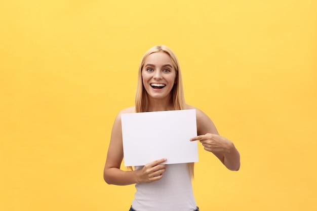 Jeune femme sur fond jaune tenant une feuille de papier vierge avec expression surprise doigt copie espace. Photo Premium