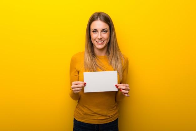 Jeune femme sur fond jaune tenant une pancarte pour insérer un concept Photo Premium