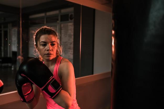 Jeune femme en formation avec un sac de boxe lourd dans la salle de gym. moment avant le coup de poing. Photo Premium