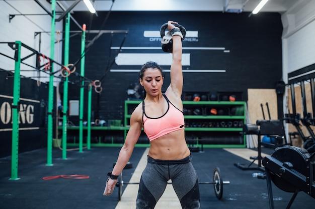 Jeune Femme Formation Swinging Kettlebell à L'intérieur Dans Un Gymnase Crossfit Photo Premium
