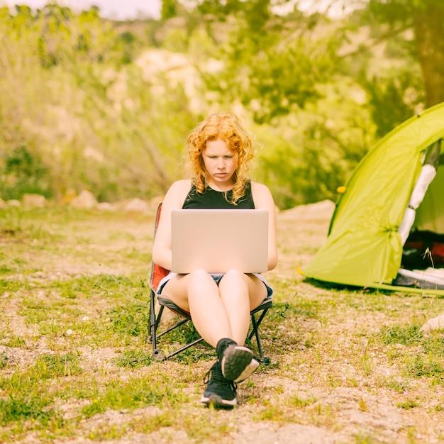 Jeune femme frisée, surfant sur ordinateur portable sur la nature Photo gratuit