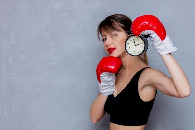 Jeune femme en gants de boxe avec réveil Photo Premium