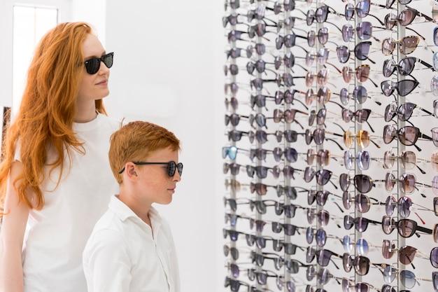 Jeune femme et garçon debout ensemble dans la salle d'exposition d'optique Photo gratuit