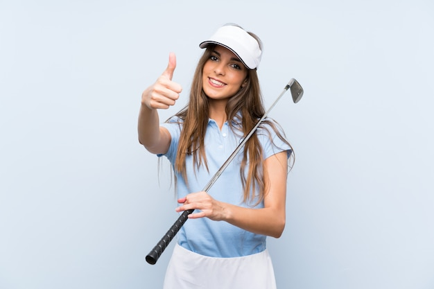 Jeune femme de golfeur sur un mur bleu isolé avec le pouce levé parce qu'il s'est passé quelque chose de bien Photo Premium