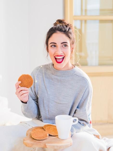 Jeune femme en gris manger Photo gratuit