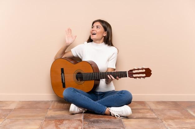 Jeune femme avec guitare assis sur le sol avec une expression faciale surprise Photo Premium