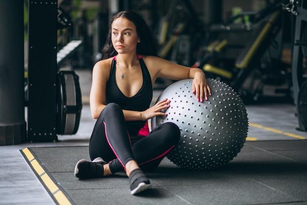 Jeune femme à la gym avec équipement Photo gratuit