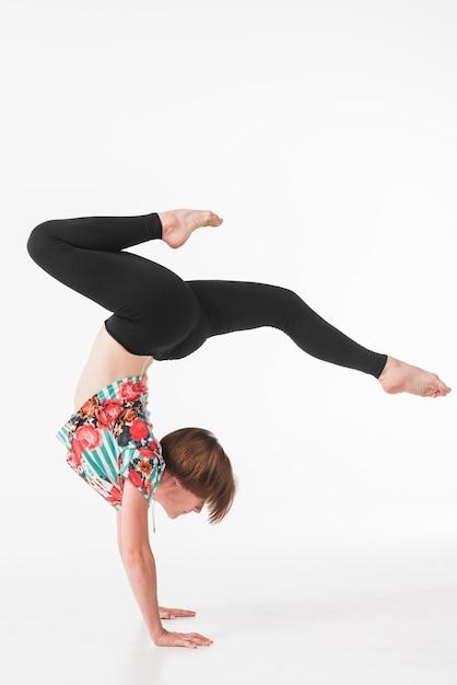 Jeune femme gymnastique dansant sur fond blanc Photo gratuit