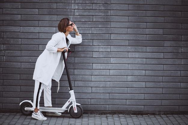 Jeune femme, habillé, blanc, équitation, scooter Photo gratuit