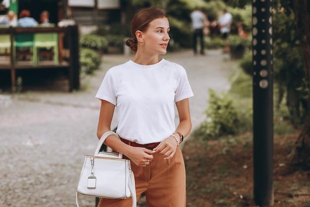 Jeune femme habillée décontractée à l'extérieur dans le parc de la ville Photo gratuit