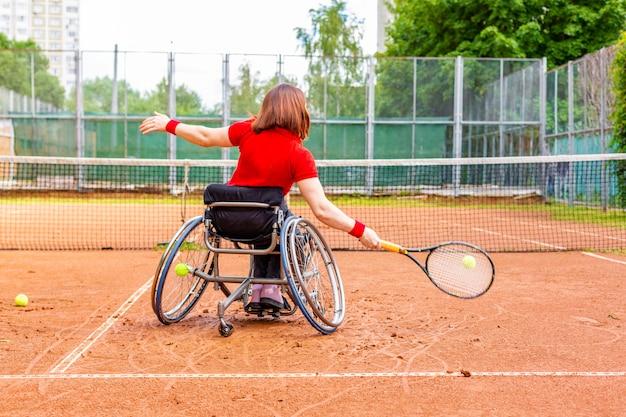 Jeune femme handicapée en fauteuil roulant jouant au tennis sur un court de tennis. Photo Premium