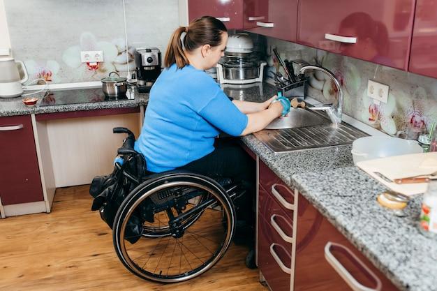 Jeune Femme Handicapée En Fauteuil Roulant, Laver La Vaisselle Dans Une Cuisine Spécialement équipée Photo Premium