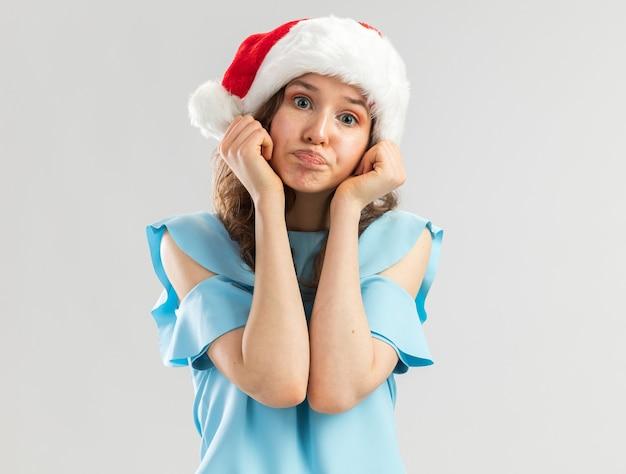 Jeune Femme En Haut Bleu Et Bonnet De Noel à Confus Faisant La Bouche Ironique Avec Une Expression Déçue Photo gratuit