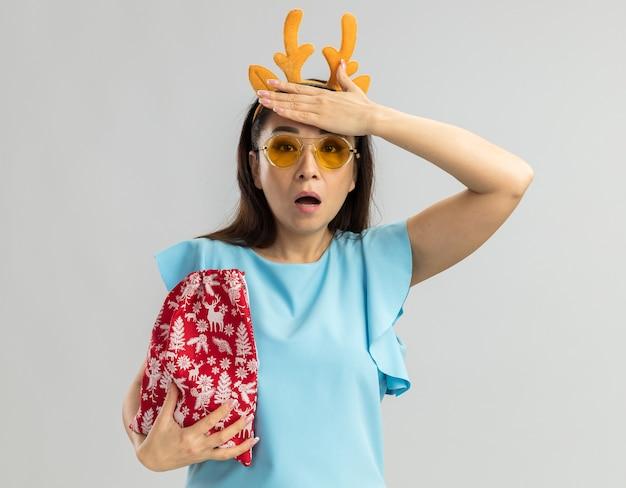 Jeune Femme En Haut Bleu Portant Une Jante Drôle Avec Des Cornes De Cerf Et Des Lunettes Jaunes Tenant Un Sac Rouge De Noël à La Confusion Avec La Main Sur Sa Tête Photo gratuit