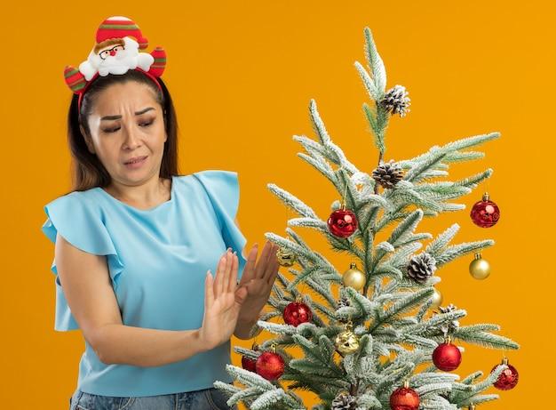 Jeune Femme En Haut Bleu Portant Une Jante De Noël Drôle Sur La Tête Debout à Côté D'un Arbre De Noël En Le Regardant Avec Une Expression Confuse Tenant La Main Sur Fond Orange Photo gratuit