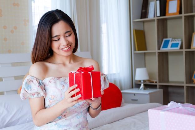 Jeune femme heureuse avec cadeau rouge dans la chambre Photo gratuit