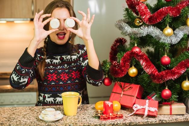 Jeune femme heureuse avec des gâteaux près de l'arbre de noël Photo Premium