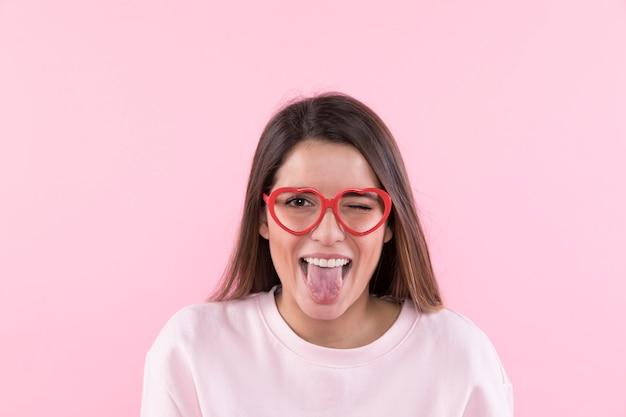 Jeune femme heureuse avec des lunettes montrant la langue Photo gratuit