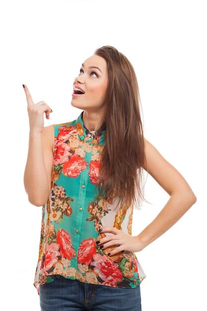 Jeune femme heureuse montre quelque chose Photo gratuit
