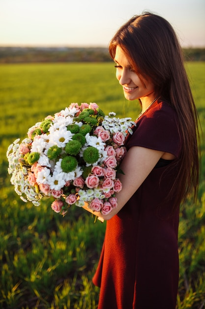 Jeune Femme Heureuse Posant Avec Un Gros Bouquet, Contre Le Coucher De Soleil Sur Le Terrain Photo Premium