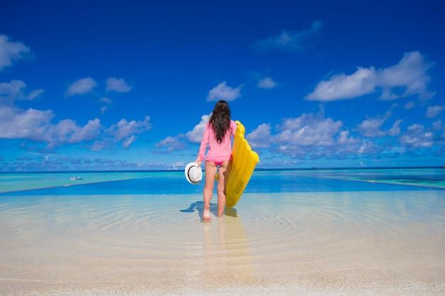 Jeune femme heureuse relaxante avec matelas pneumatique pendant les vacances tropicales Photo Premium